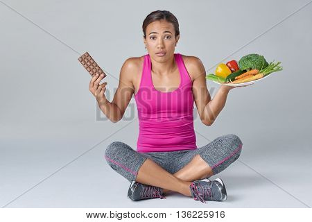 portrait of a confused woman in dilemma with chocolate and vegetables, healthy eating choices balance scale concept
