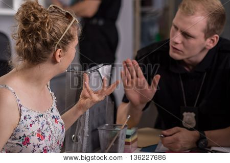 Nervous woman at a police station and policeman trying to calm her down