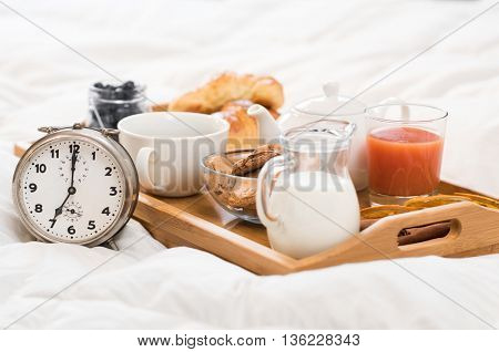 Breakfast in bed with tea and croissants. Healthy breakfast served on a tray on bed with alarm clock. French breakfast with milk, orage juice, cookies, tea, and brioches.
