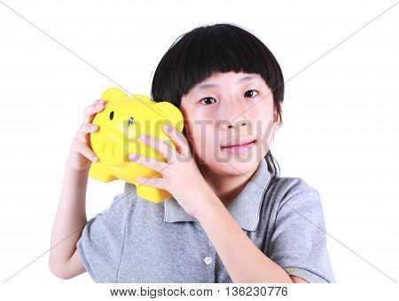Young boy holding yellow piggy bank isolated on white.