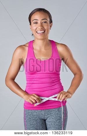 Slim sporty woman measuring waistline, healthy living wellness weight loss concept