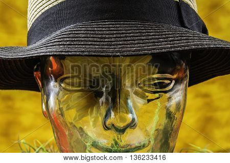 clear glass human head with sunflower inside wearing black and white hat on yellow background