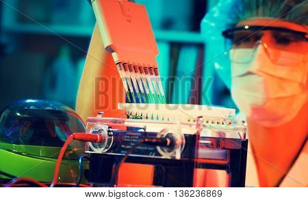 Researcher using a multi-pipette to fill a multiwell sample tray in a biochemistry lab.