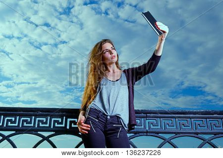 Young beautyful women use phablet for selfie photography in bright day against cloudy sky, toned image, colorized, instagram-like color filter.