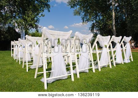 Back decorated chairs. White decorated chairs on a green lawn. Chairs set in rows for the wedding ceremony. They are decorated for the festive event. Chairs are on the green lawn outside.
