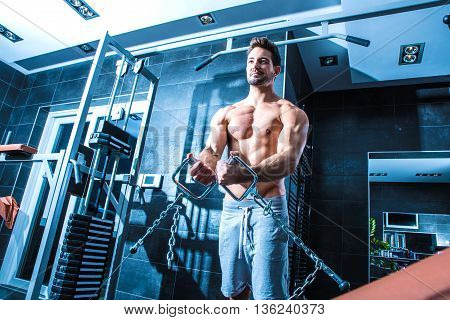 A young man practicing bodybuilding and weight lifting in the Gym.