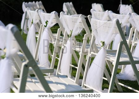 White chair with a small flower. White decorated chairs on a green lawn. Chairs set in rows for the wedding ceremony. They are decorated for the festive event. Chairs are on the green lawn outside.