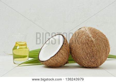 Healthy Coconut Oil, Tropical, Beauty Spa Concept - Close Up Of Coconut Shell Cut Half With Green Le