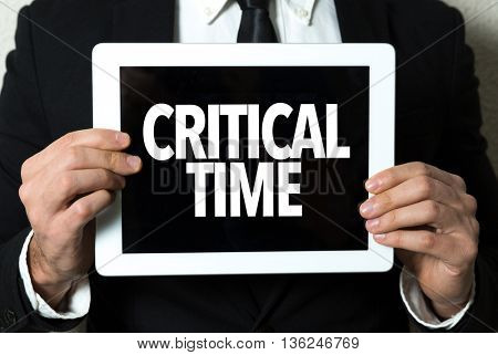Business man holding a tablet with the text: Critical Time