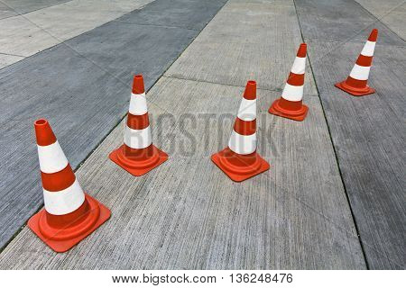 Traffic cones on a concrete parking lot.