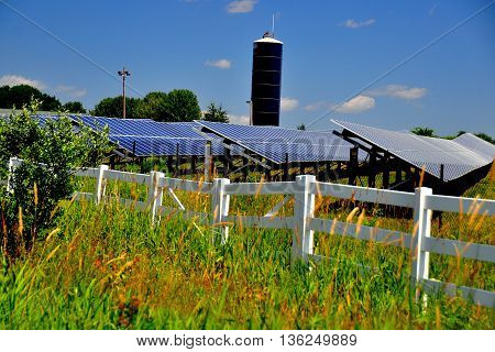 Connecticut - July 10,  2015: Rows of solar panels soak up the sun at a Solar Energy Farm on a countryside road *