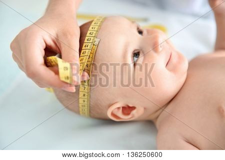 Professional pediatrician examining smiling baby