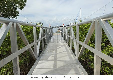 White wooden footbridge leads from the marina to the mainland Fort Myers. Florida