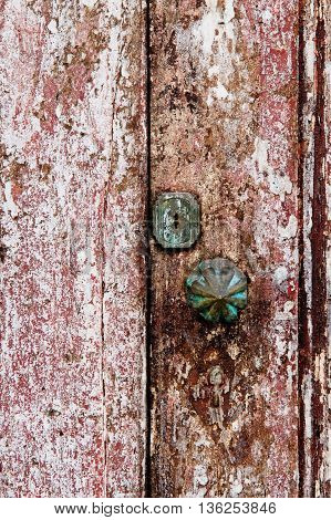 Old grungy wooden door with peeling paint and round door-handle