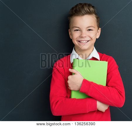 Happy pupil - teen boy posing with books in front of a big chalkboard. Back to school concept.