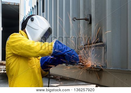 Industry worker with grinding metal to repair container structures manufacture workshop. Worker grinding in factory industry.