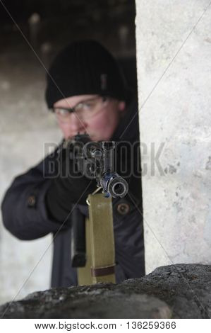 machine gunner in black uniforms and protective glasses aim of the shelter