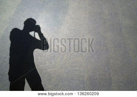 Photographer shade from the sun on the asphalt