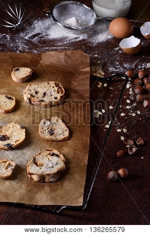 Baked bread rusks with raisins and nuts, cooking ingredients over rustic kitchen table. Brussels hazelnut biscuits, crispy appetizers.