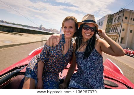 Female friends on holidays people traveling young women having fun on vacation two happy girls smiling in Havana Cuba. Hispanic persons laughing on old classic convertible car. Slow motion