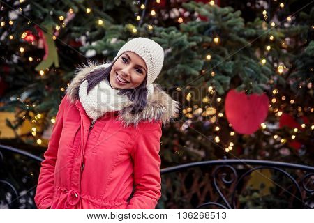 Portrait of a beautiful young woman next to a big christmas tree on the christmas market.