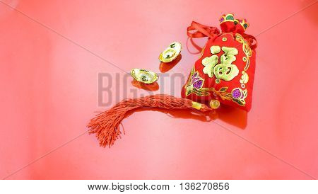 "Chinese new year decoration: red felt fabric packet or ang pow with word ""prosperous"" and golden ingots on red fabric. poster"