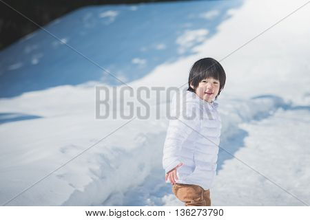 Portrait of asian boy in winter clothes with snow background