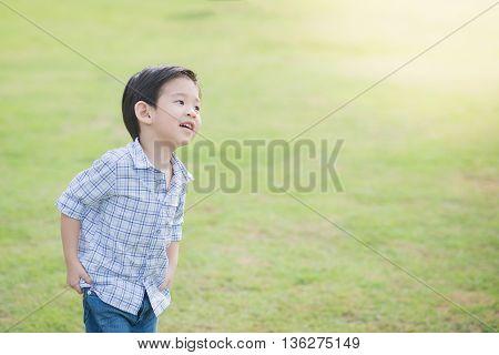 Cute Asian chid running on green grass under sunlight