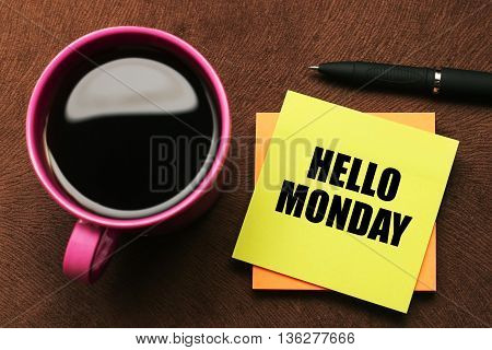 Hello Monday - text on sticky note with a pen and cup of coffee