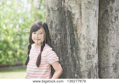 Happy little asian girl having fun at the park