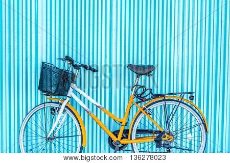 A bicycle with basket leaning against blue corrigated iron fence
