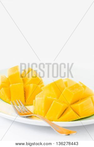A delicious mango ripe and ready to eat on a white plate with white background.