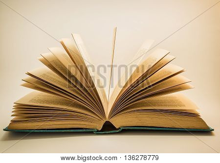 An old open story book on a white background with the pages fanning out.