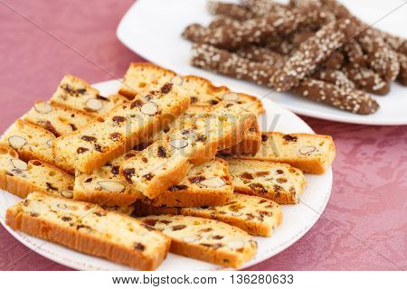 Carob crackers and crackers with nuts and raisins in plates on pink cloth background.