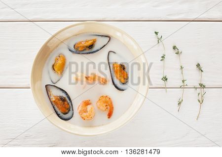 Bowl of seafood cream-soup with rosemary flat lay. Top view on bowl with white cream-soup with mussels and shrimps on white wooden background, decorated with rosemary, void. Creative food decoration
