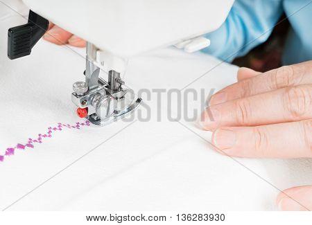 Seamstress using sewing machine close-up. Woman hand sewn white cloth