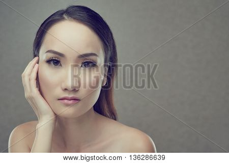 Portrait of unsmiling Asian woman, isolated on grey