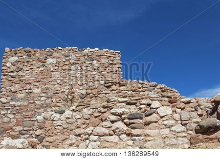 Section of stone wall from ancient Sinaguan Indian pueblo, Tuzigoot National Monument, in Clarkdale, Arizona against a clear blue sky.