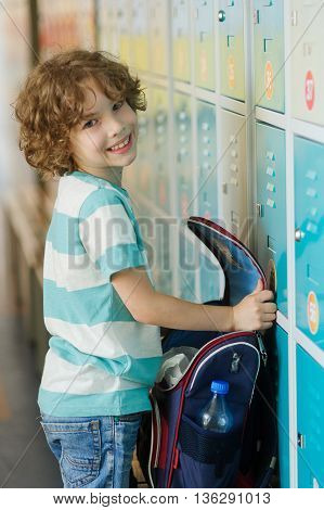 The primary school students standing near lockers in school hallway. He put the backpack on the bench and something it's looking for. Boy smiling.