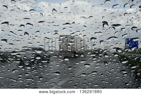 Safety driving. Rain drops on car windshield at the highway