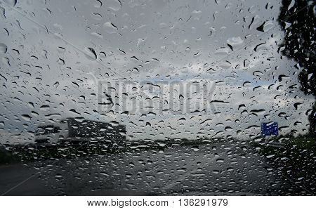 Look on truck on the highway through wet windshield with rain drops
