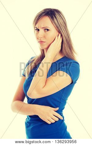 Young casual woman touching her ear.