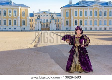 Historical cosplay. Beautiful woman in the similitude of Isabella d'Este Mantua marquess of Italian ancient dress near palace