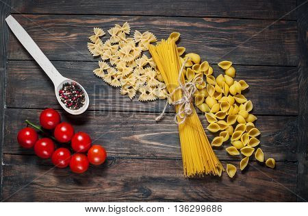Italian pasta on a wooden table. Bunch tomatoes and wooden spoon with spice. Top view