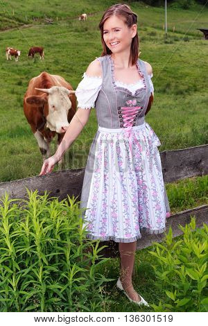 Portrait of a young peasant woman in dirndl that looks laughing at the camera.