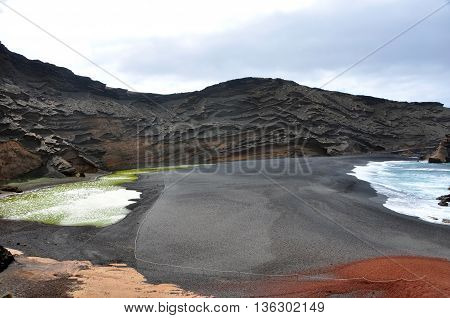 black lava sand beach with green water at El Gordo on spanish volcanic island Lanzarote