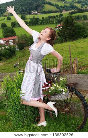 Bavarian Girl in Dirndl leans on a bicycle as a plant stand and stretches for joy right arm in the sky