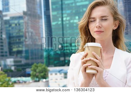 Cheerful business woman blonde holding coffee outdoors on city background