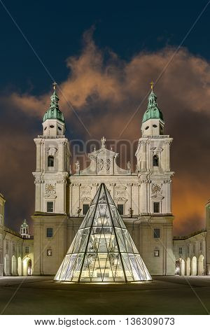 The Salzburg Cathedral (Salzburger Dom) illuminated at night with the fountain protected by a glass structure.