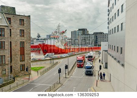 ABERDEEN SCOTLAND - JUNE 21 2016:Trinity Quay Aberdeen with offshore supply ships moored and commercial vehicles on the road.